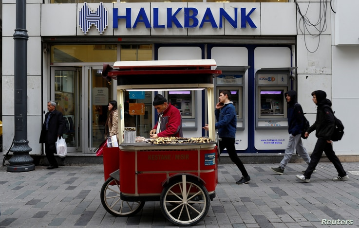 A street vendor sells roasted chestnuts in front of a branch of Halkbank in central Istanbul, Turkey, Jan. 10, 2018.