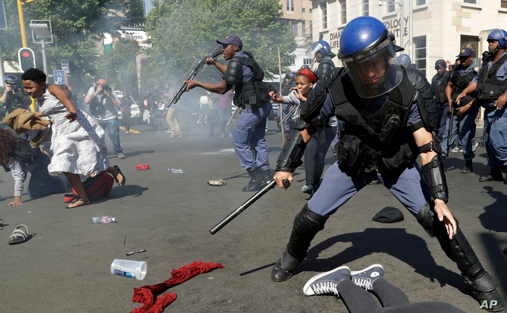 Students run for cover as police fire stun grenades and rubber bullets in an attempt to disperse them, during their protest for free education in Johannesburg, South Africa, Sept. 21, 2016.