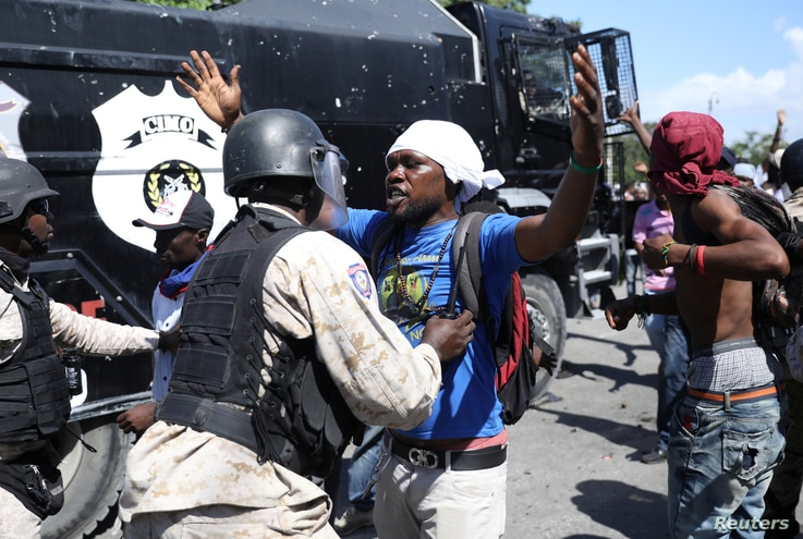 A Haitian National Police officer pushes a protester during a march to demand an investigation into what they say is the alleged misuse of Venezuela-sponsored PetroCaribe funds, in Port-au-Prince, Haiti, Oct. 17, 2018.