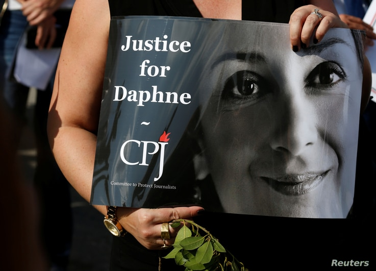 A person holds a placard depicting Daphne Caruana Galizia, prepared by Committee to Protect Journalists (CPJ), as people gather at the site where anti-corruption journalist was assassinated in a car bomb one year ago, in Bidnija, Malta, Oct. 16, 2018