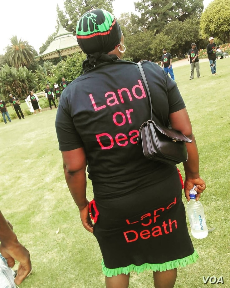 """A woman activist is seen at the rally sporting clothing with the slogan """"Land or Death"""" reprentative of the uncompromising stance taken by activists on land redistribution. (A. Powell/VOA)"""
