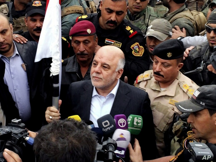 Iraqi Prime Minister Haider al-Abadi, center, raises an Iraqi flag in the city of Ramadi, 70 miles (115 kilometers) west of Baghdad, after it was retaken by the security forces, Dec. 29, 2015.