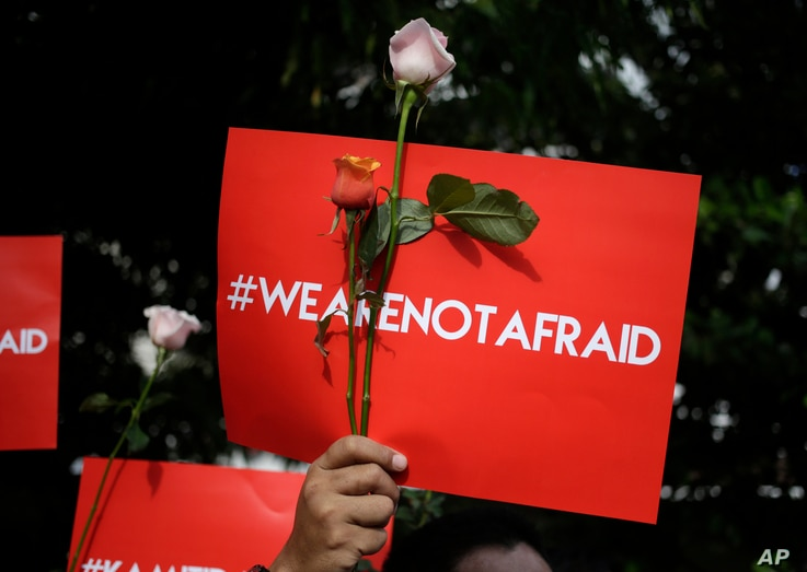 An activist holds a poster during a rally condemning a Jan. 15, 2016 attack, outside a cafe where it took place in Jakarta, Indonesia. Indonesians were shaken but refusing to be cowed a day after a deadly attack that has been claimed by the Islamic S...