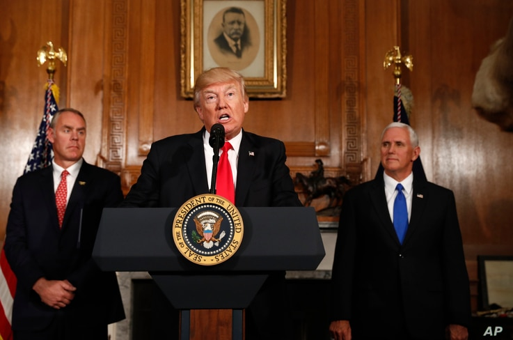 FILE - President Donald Trump, flanked by Interior Secretary Ryan Zinke, left, and Vice President Mike Pence, speaks at the Interior Department in Washington, Wednesday, April 26, 2017, before signing an Antiquities Executive Order.