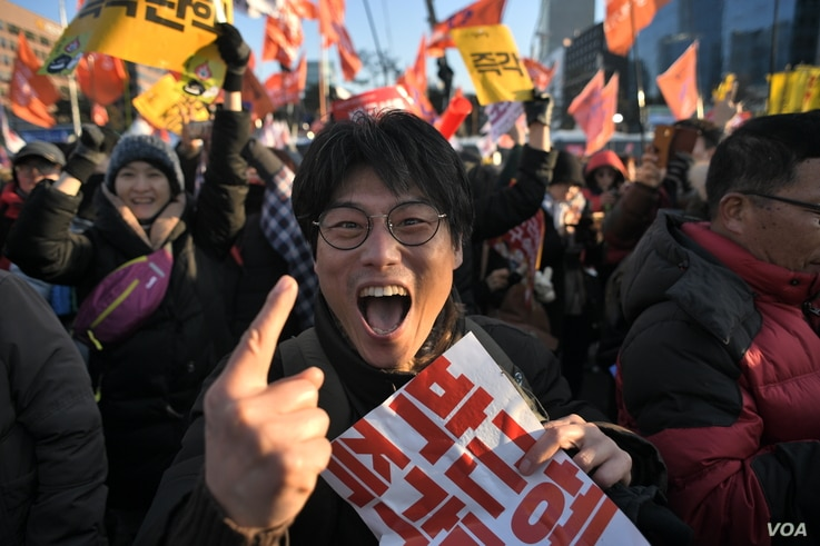 A protester reacts after the South Korean parliament's successful impeachment of President Park Geun-Hye as crowds gather outside the National Assembly in Seoul, Dec. 9, 2016.