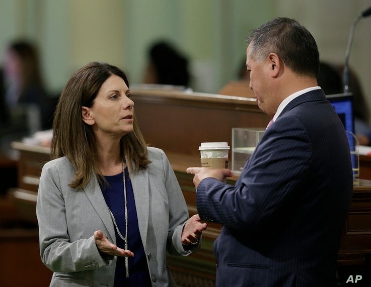 Assemblywoman Melissa Melendez, R-Lake Elsinore, talks with Assemblyman Phil Ting, D-San Francisco, as the Assembly debates Ting's soda tax measure, June 28, 2018, in Sacramento, Calif. Lawmakers passed the bill to ban local taxes on soda for the nex...