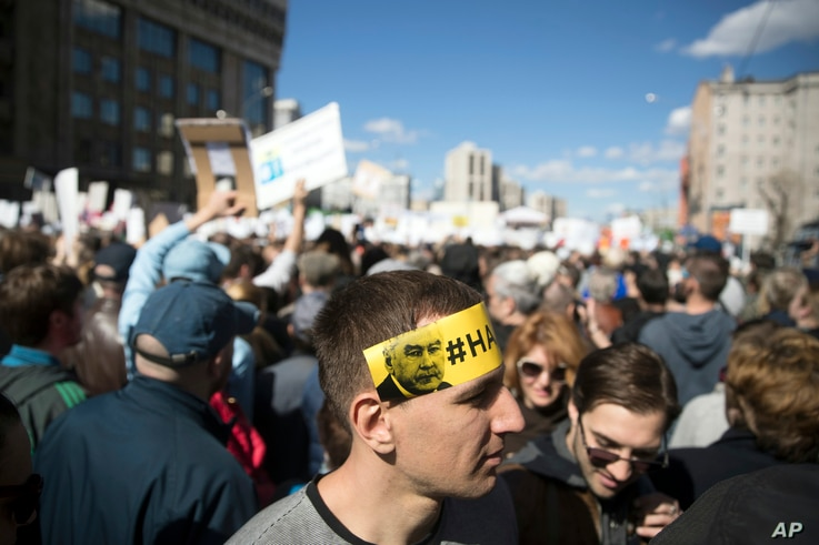 A man displays a sticker on his head with portrait of Moscow mayor Sergei Sobyanin reading 'Enough!', as people gather for a rally in Moscow, Russia, May 14, 2017.