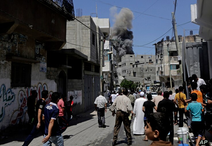 Smoke and dust billow in the distance after an Israeli strike hit Gaza City, northern Gaza Strip, Thursday, Aug. 21, 2014.