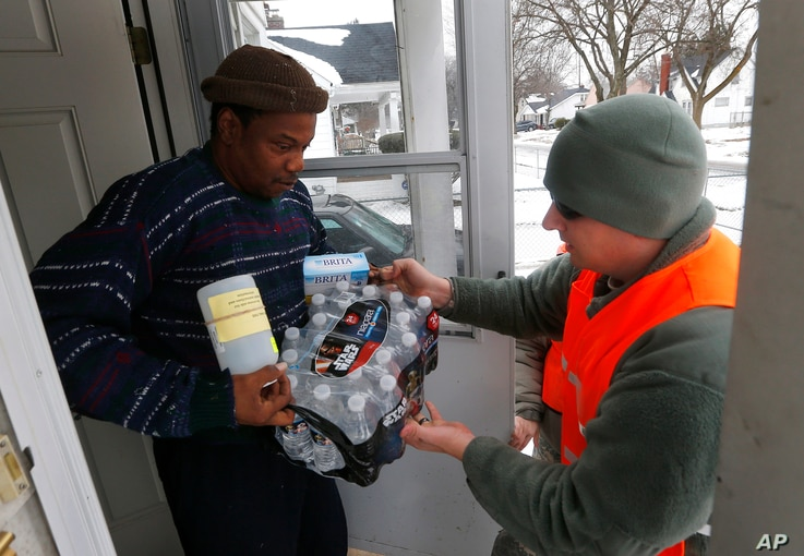 Louis Singleton receives water filters, bottled water and a test kit from Michigan National Guard Specialist Joe Weaver as clean water supplies are distributed to residents,  Jan. 21, 2016 in Flint, Mich.