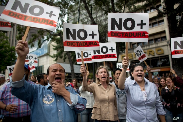"People holding signs with a message that reads in Spanish: ""No more dictatorship"" take part in a walkout against President Nicolas Maduro, in Caracas, Venezuela, Jan. 30, 2019."