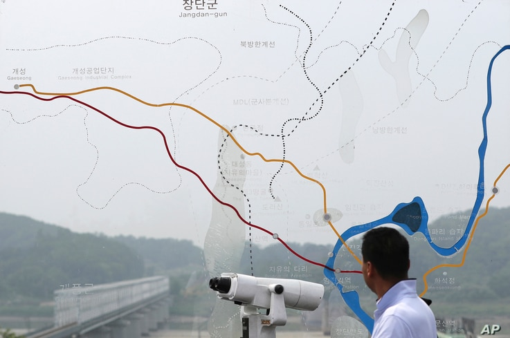 A man watches the north side through the glass showing a map of the border area between North and South Koreas at the Imjingak Pavilion near the Panmunjom, which has separated the two Koreas since the Korean War, in Paju, South Korea, July 6, 2017.