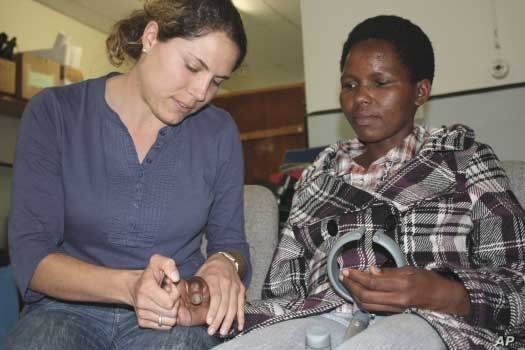 The physiotherapist examines her patient's paralyzed right hand