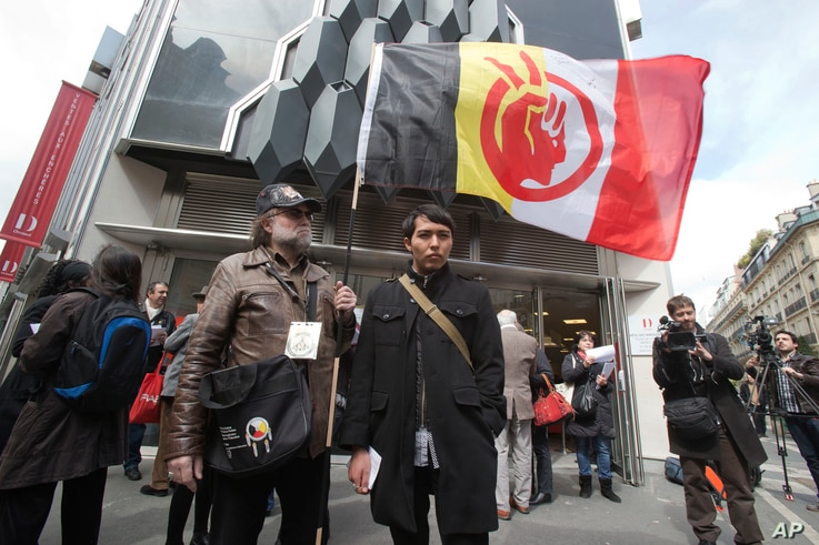 A French supporter of the Indian cause, who refused to give his name, left, holds a flag of the American Indian Movement and an American exchange student, member of the Arizona's Hopi tribe, Bo Lomahquahu, right, stand outside of the Druout's auction...