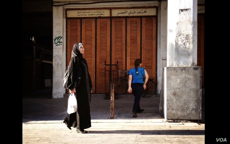 A veiled woman walks down the street in Damascus's old city. (J. Weeks/VOA)
