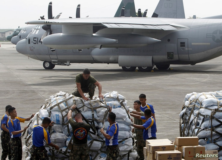 Philippine and U.S. military personnel prepare to load relief goods on a U.S. C-130 plane for victims of Typhoon Haiyan that hit the central Philippines, at Villamor Air Base in Manila, Nov. 11, 2013.
