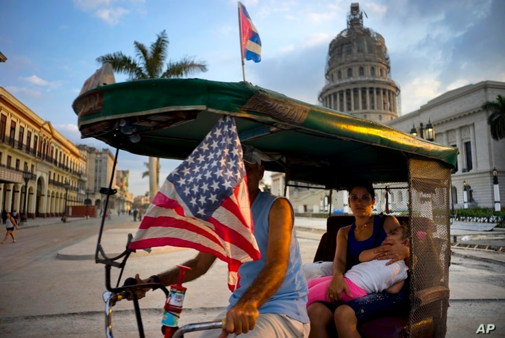 A taxi pedals his bicycle, decorated with Cuban and U.S. flags, as he transports a woman holding a sleeping girl, near the Capitolio in Havana, Cuba, March 15, 2016.