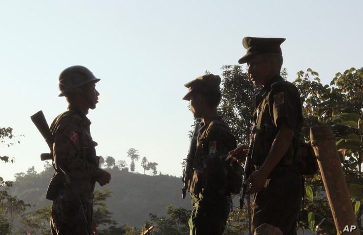FILE - Three Kachin Independence Army (KIA) soldiers patrol along the bunker at the front line of on a mountain near Laiza, the headquarters of KIA in Kachin State, Myanmar. Nov. 30, 2016.