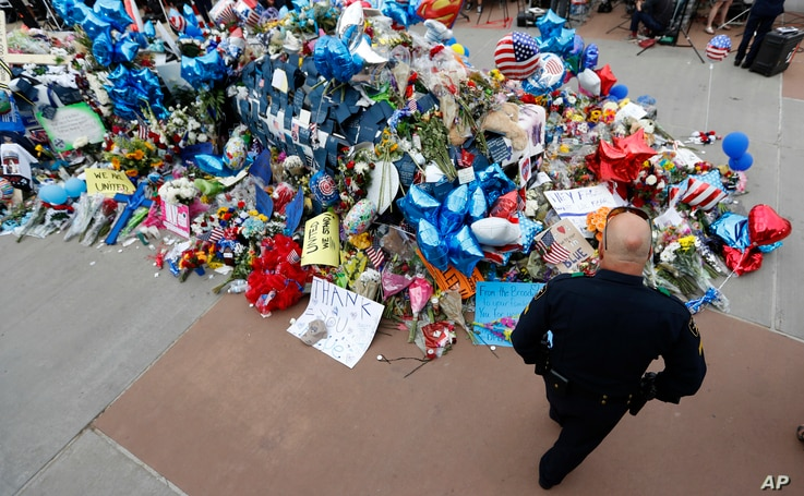 A policeman visits a makeshift memorial at the Dallas police headquarters, July 11, 2016, in Dallas.
