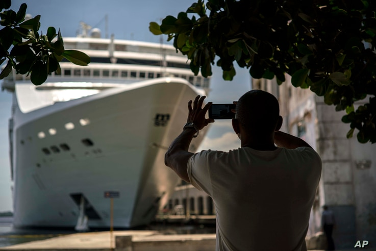 FILE - In this June 17, 2017, photo, a man takes a photo of a cruise ship in Havana harbor, Cuba.