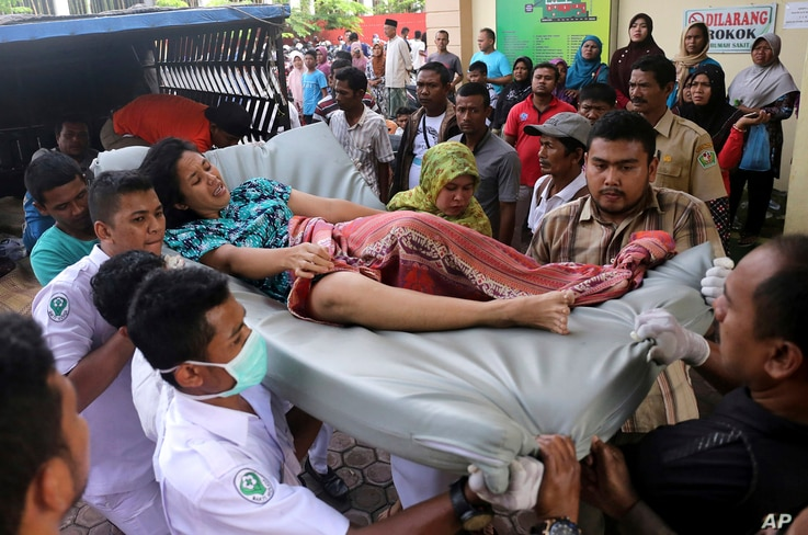 Hospital workers and family members carry a woman injured in an earthquake at a hospital in Pidie, Aceh province, Indonesia, Dec. 7, 2016.