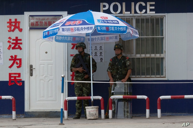FILE - Chinese paramilitary police stand on duty in front of a wanted poster in the city of Aksu in western China's Xinjiang province, July 17, 2014.  China has blanketed parts of Xinjiang, home to Muslim, Turkic-speaking Uighurs, with heavy security...