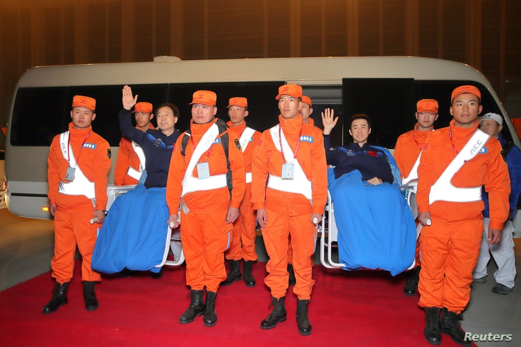 Chinese astronauts Jing Haipeng (left, in blue) and Chen Dong, who landed safely aboard China's Shenzhou 11 spacecraft's re-entry capsule in the northern region of Inner Mongolia, arrive in Beijing, China, Nov. 18, 2016.