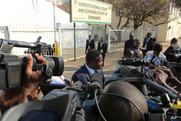 Zimbabwean President Emmerson Mnangagwa's legal representative Paul Mangwana talks to the media outside the Constitutional Court in Harare, Aug. 22, 2018.