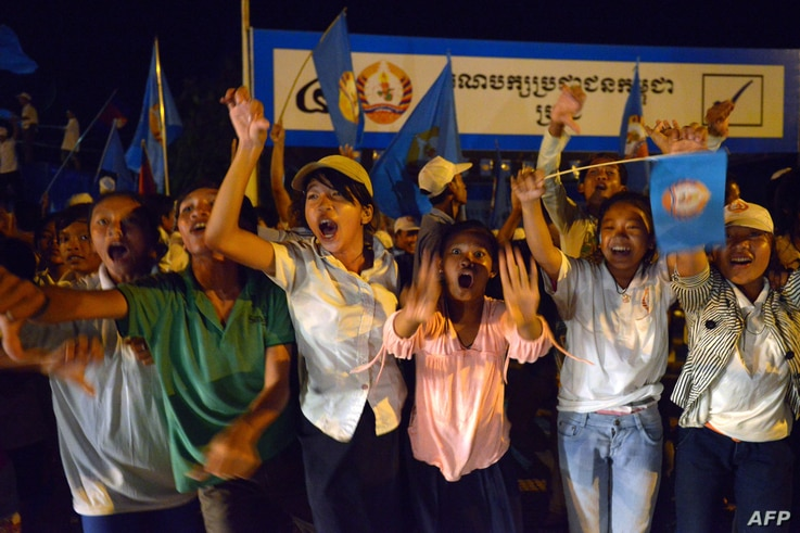 Supporters of the Cambodian People's Party (CPP) shout slogans during a general election campaign in Kandal province, July 12, 2013.