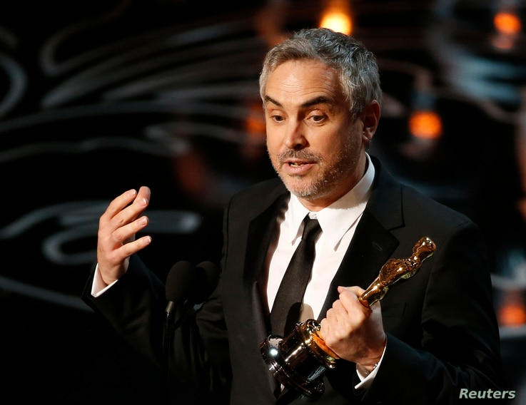 """Alfonso Cuaron accepts the Oscar for best director for """"Gravity"""" at the 86th Academy Awards in Hollywood, CA. March 2, 2014."""