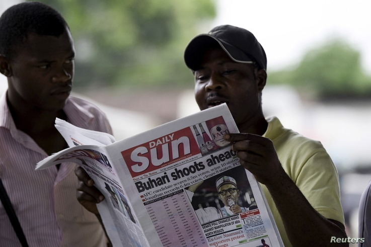 A man reads a newspaper with a headline related to the country's elections, at a news stand at Port Harcourt, in the Rivers state March 31, 2015. Nigeria's opposition contender Muhammadu Buhari held a sizeable lead as counting in the country's electi