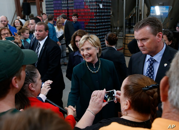 Democratic presidential candidate Hillary Clinton shakes hands with the audience during a campaign stop at Jackie O's Production Brewery and Tap Room in Athens, Ohio, May 3, 2016.