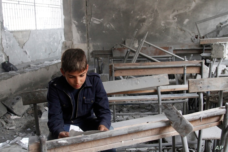 FILE - A boy reads a torn paper inside a classroom in his destroyed school in Aleppo, Syria.