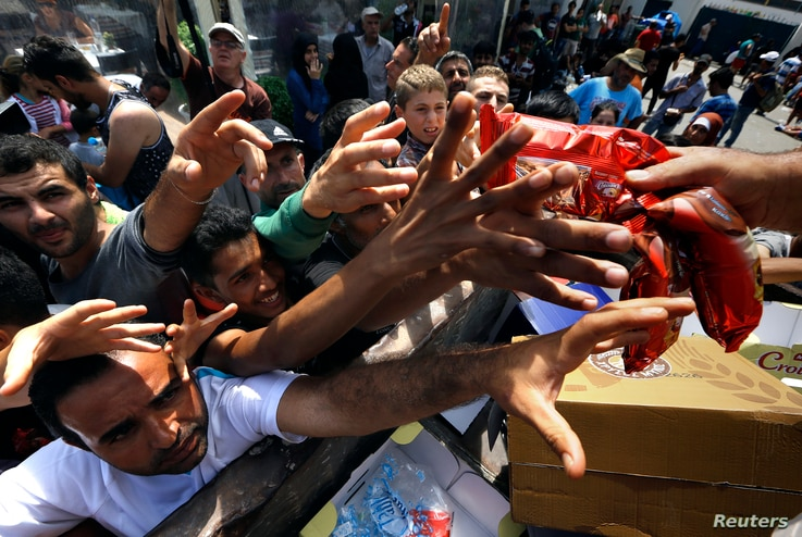 Syrian refugees and other migrants struggle to get dry food during aid distribution by municipality workers on the Greek island of Kos, Aug. 14, 2015.