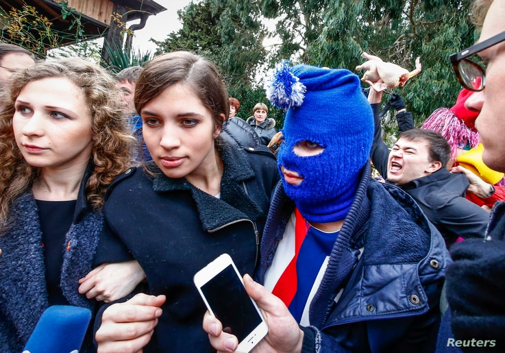 Russian punk band Pussy Riot members Maria Alyokhina (L) and Nadezhda Tolokonnikova (2nd L) along with a masked member speak to journalists during the 2014 Sochi Winter Olympics, in Adler February 20, 2014. The band was supposed to hold a news confer...