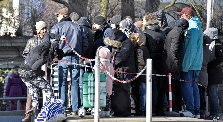 """People wait in front of the food bank """"Tafel"""" for free food in Essen, Germany, Feb. 24, 2018. Essen's division of the charitable organization announced not to take any new migrant customers because their number rises up to 75 percent and would block ..."""