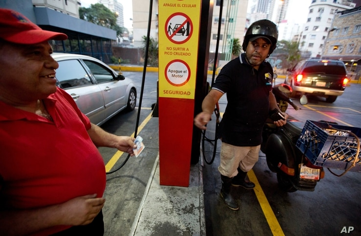 A motorcyclist pays about two Bolivars (3 cents of a dollar) after filling his scooter's tank at a gas station in Caracas, Venezuela, Feb. 17, 2016.