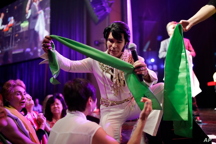 """Ted Torres hands out scarves to fans at the """"Images of the King: Las Vegas"""" festival in Las Vegas, July 15, 2017. Fans at performances will line up along the stage to receive the sweat-soaked souvenirs from performers."""