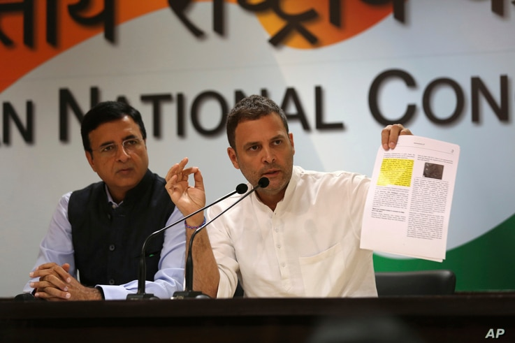 India's Congress party President Rahul Gandhi displays documents as he accuses Narendra Modi's government of buying 36 Rafale fighter jets from France's Dassault at a highly inflated price, in New Delhi, India, Oct. 11, 2018.
