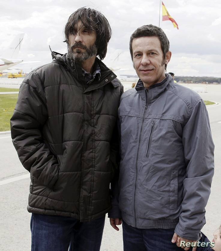 Freed El Mundo Middle East correspondent Javier Espinosa (R) and freelance photographer Ricardo Garcia Vilanova pose after their arrival at Torrejon de Ardoz airbase near Madrid March 30, 2014. The two Spanish journalists held hostage in Syria by an