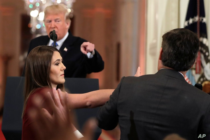 As President Donald Trump points to CNN's Jim Acosta, a White House aide takes the microphone from the reporter during a news conference in the East Room of the White House, Nov. 7, 2018, in Washington.