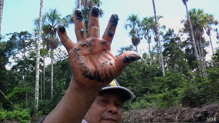 A local resident shows the oil residue left behind along an Amazon tributary from a pipeline. (Credit: International Wow Company)