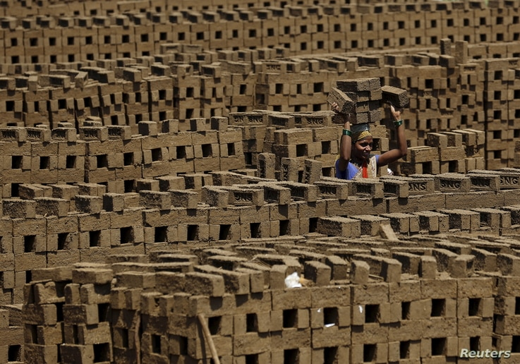 A laborer carries bricks at a kiln in Karjat, India, March 10, 2016.
