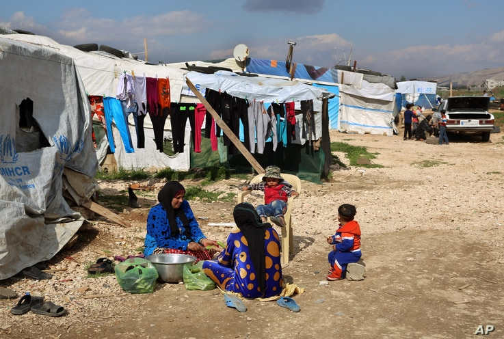 Syrian women prepare food for their family outside their tents, at a Syrian refugee camp in the town of Bar Elias, in Lebanon's Bekaa Valley, March 29, 2016.
