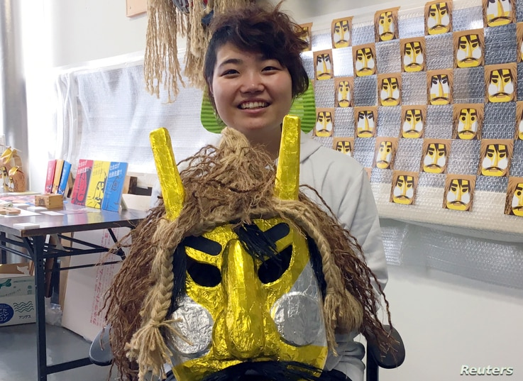 Kokoro Ohtani, 24, an employee of Oga City Hall, holds a Namahage mask as she poses for a photogarph during an interview with Reuters in Oga, Japan, Feb. 8, 2019.