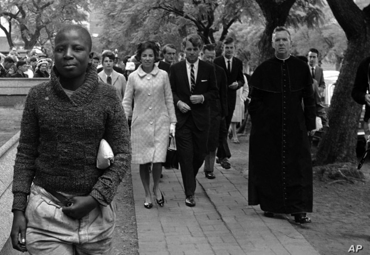 FILE - In this June 5, 1966, file photo Sen. Robert F. Kennedy, back right, and his wife, Ethel, back left, arrive at the Roman Catholic Cathedral in Pretoria, South Africa, during a visit to the country.