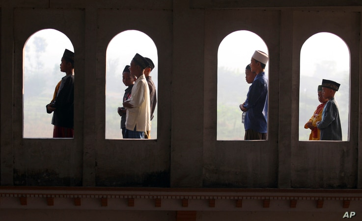 Muslim youths are seen through the windows of a mosque as they perform Eid al-Fitr morning prayers, Porong, East Java, Indonesia, August 8, 2013.