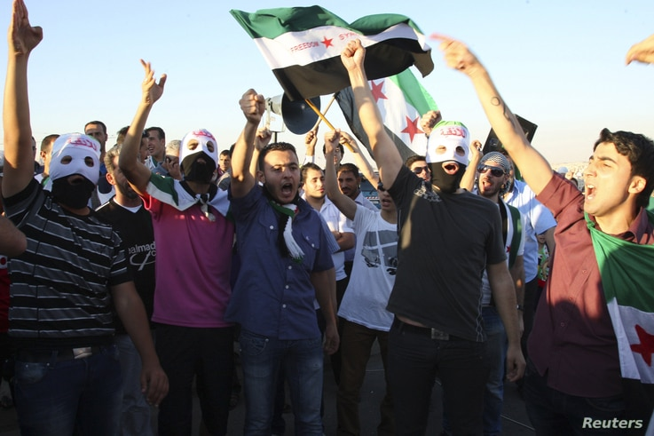 Syrian protesters wave Syrian opposition flags as they shout slogans against Syrian President Bashar Al-Assad outside the Syrian embassy in Amman, July 5, 2012.