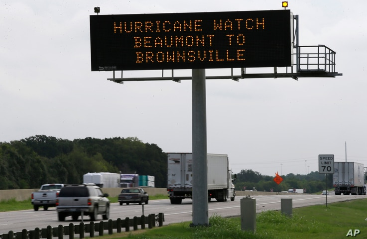 A sign warns of a Texas coastal hurricane watch as traffic passes by in Hutchins, Texas, Thursday, Aug. 24, 2017. A hurricane warning was issued for most of the central and southern Texas coast Thursday morning.