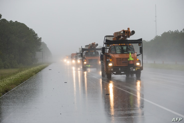 Tree-trimming trucks head into Biloxi, Miss., which was under a hurricane warning as Hurricane Nate approached the Mississippi Gulf Coast, Oct. 7, 2017.