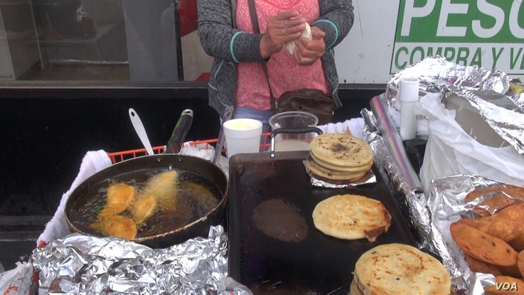 A vendor in Los Angeles, Calif., prepares pupusas, center, and other savory Salvadoran street food. The city council unanimously voted to decriminalize sidewalk sales. (A. Martinez/VOA)